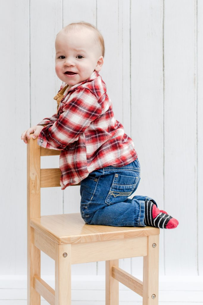baby and toddler sit and play on a wooden chair in a studio with a white wooden backdrop