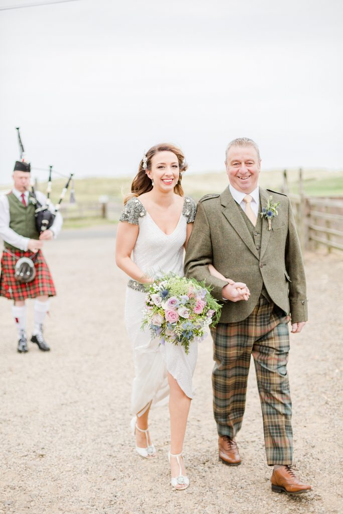 Bride and father of the bride walking bagpiper following