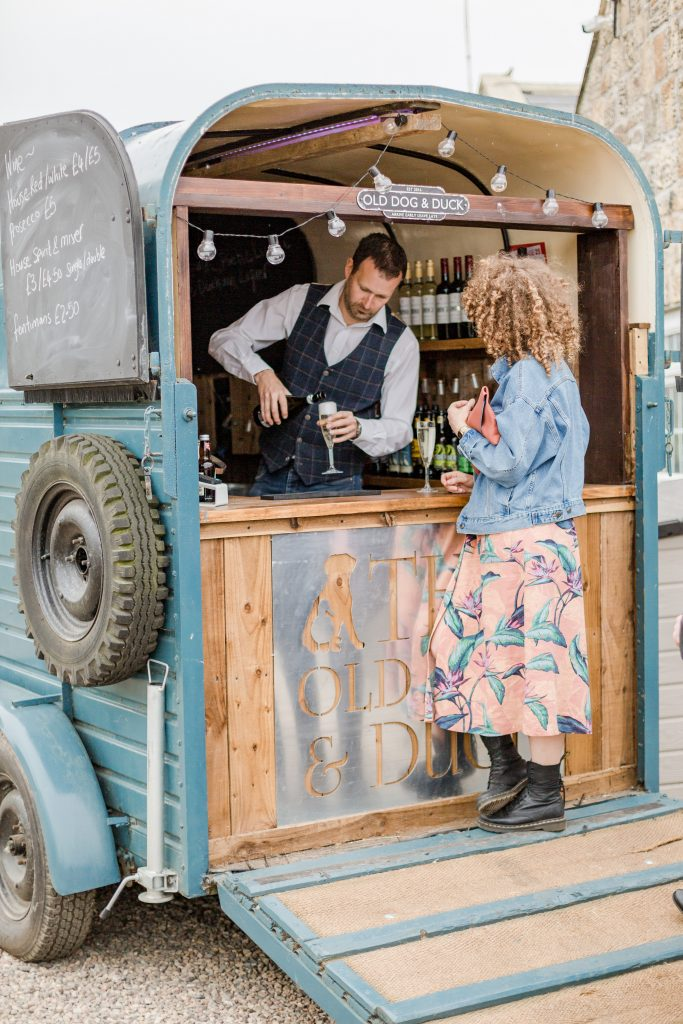 barman at horse box bar pouring wedding guest a drink