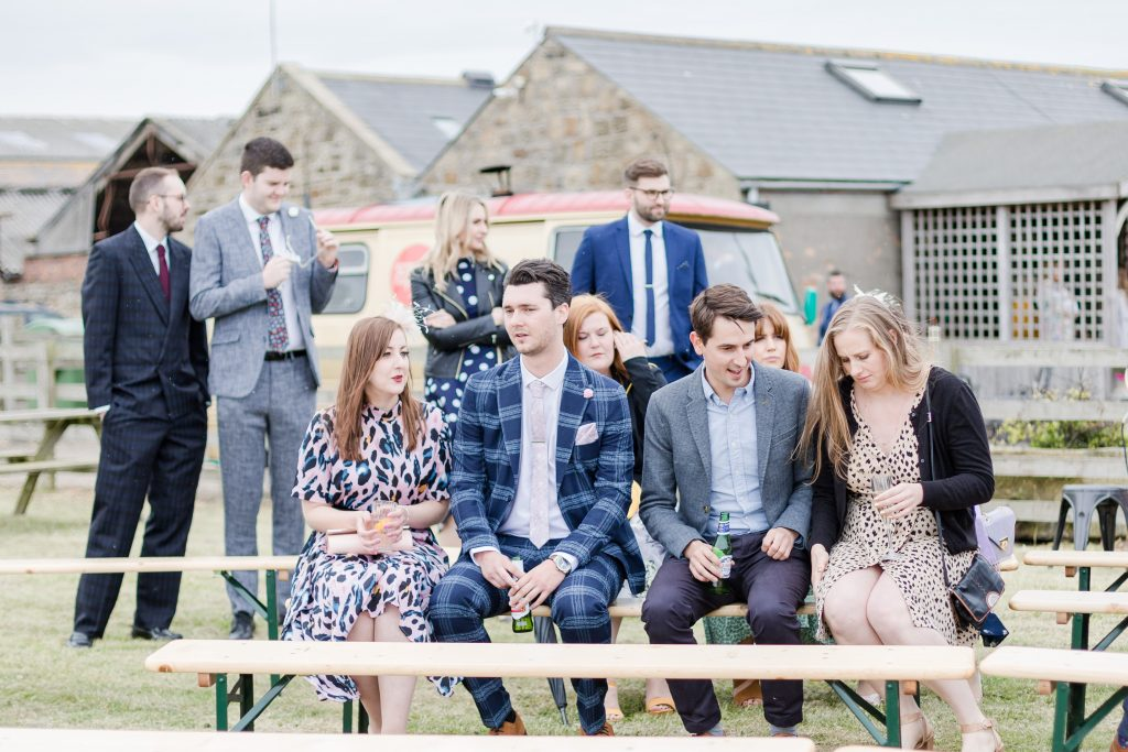 wedding guests sat on bench at festival style wedding