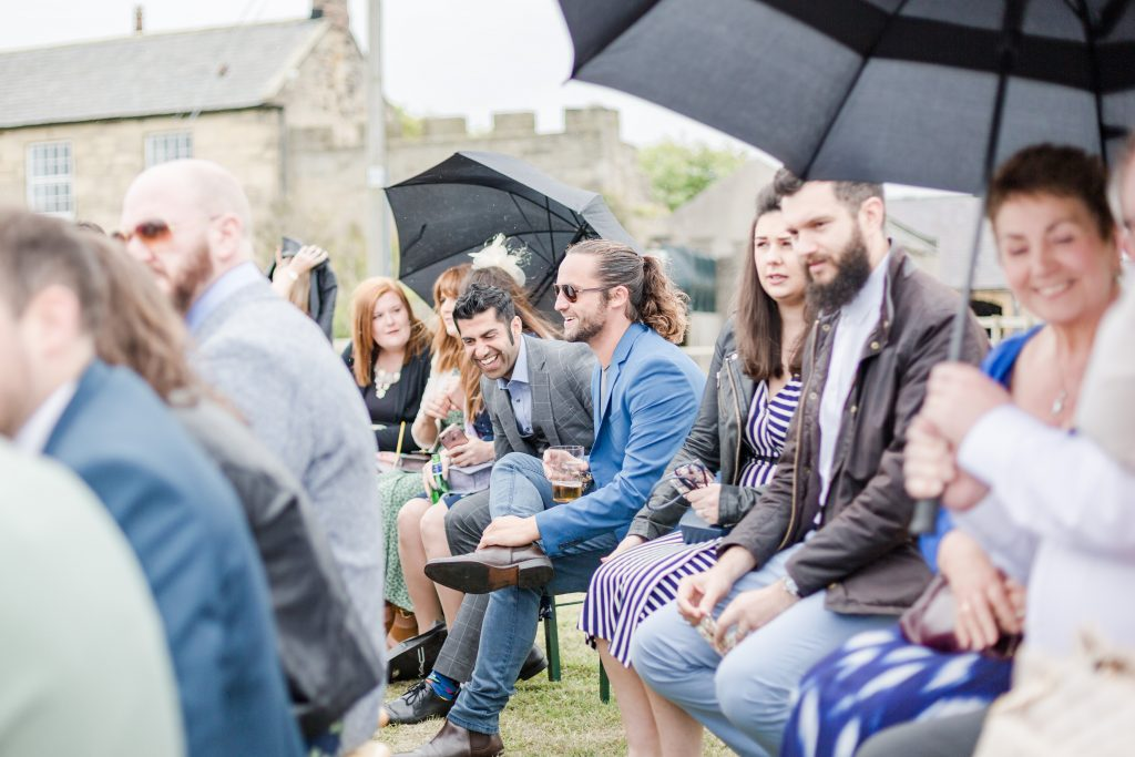 wedding guests sat on bench laughing under umbrella at festival wedding