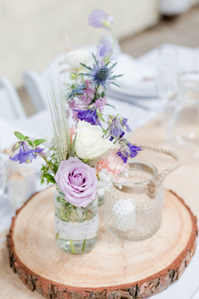 roses thistles and purple flowers in jam jars on wooden slices