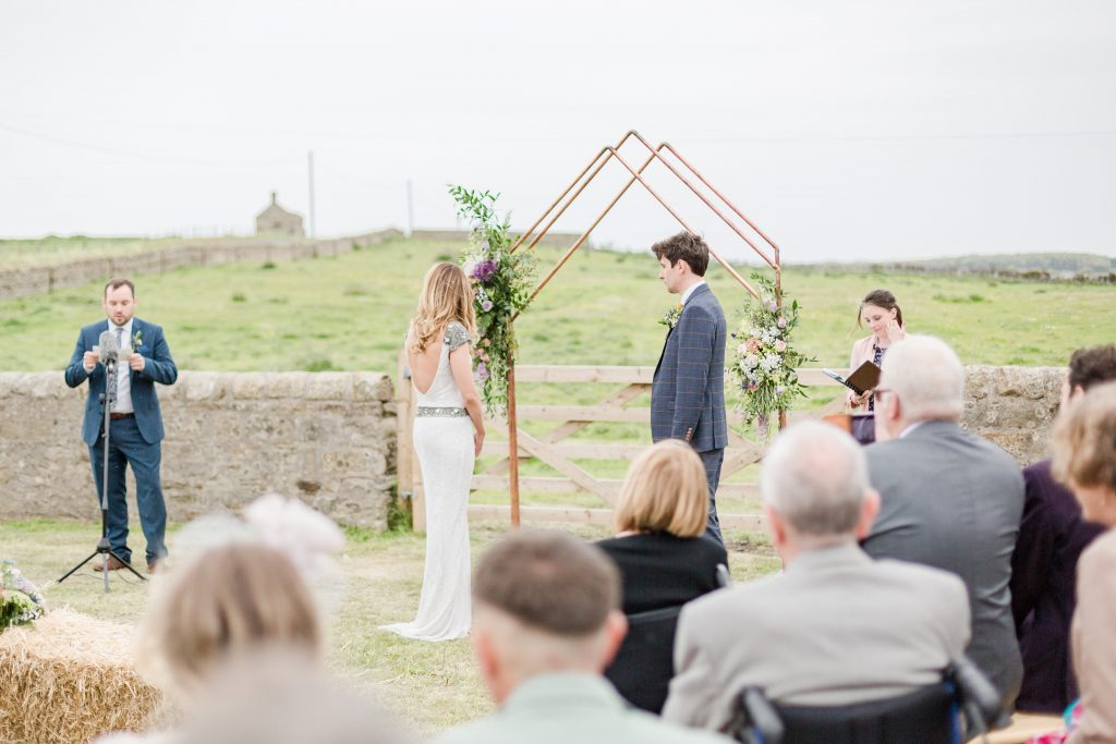 bride and groom turn to look at guest doing reading in wedding field