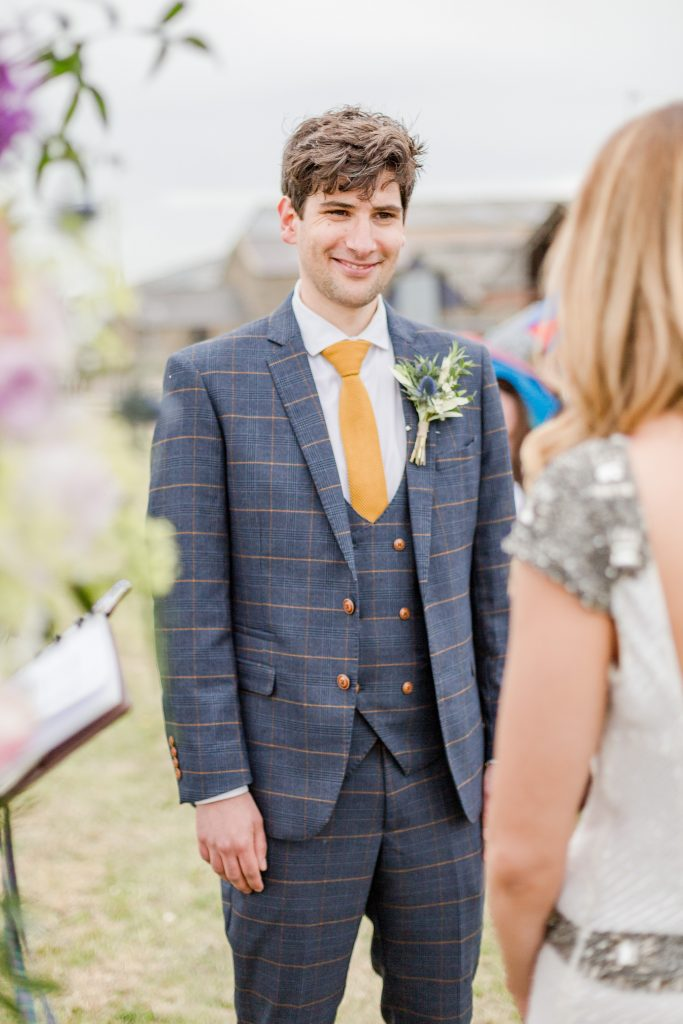 groom smiling at bride at outside wedding ceremony