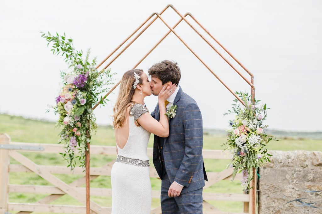 bride and groom kissing under copper arch at outside ceremony