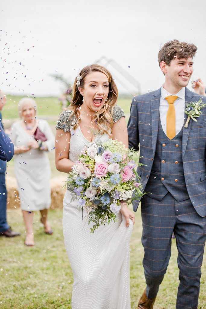 bride and groom walking under confetti in field