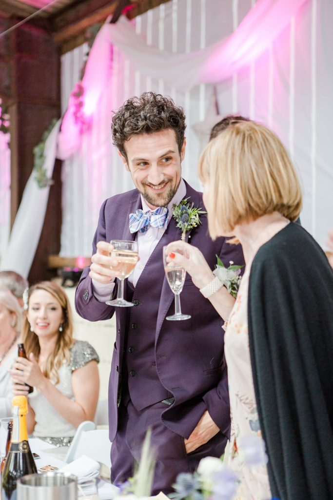 brother of groom clinking glasses with mother at top table