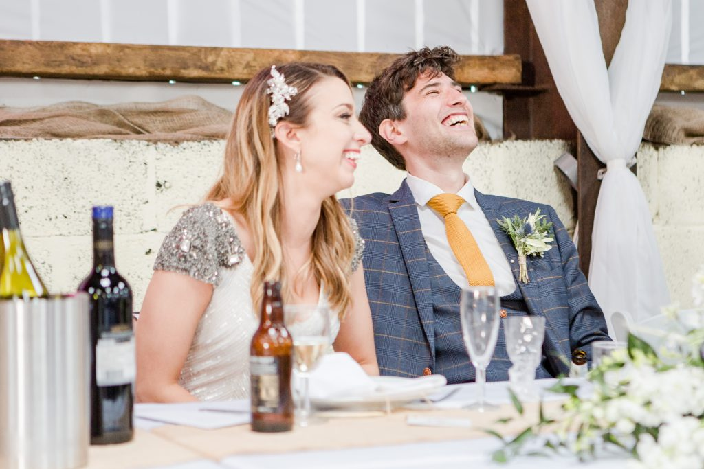 bride and groom sat at top table laughing