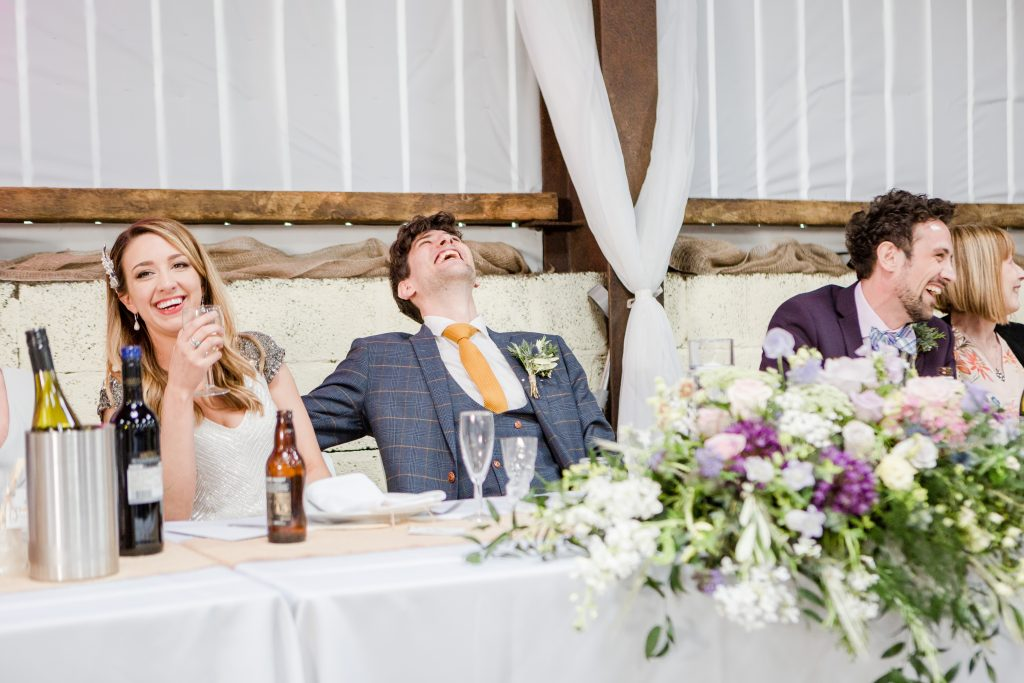 groom throwing head back in laughter at top table