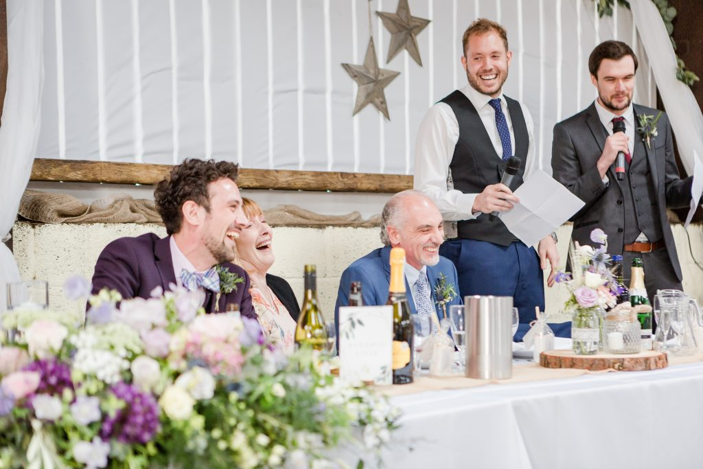 top table all laughing at two groomsmen giving speeches