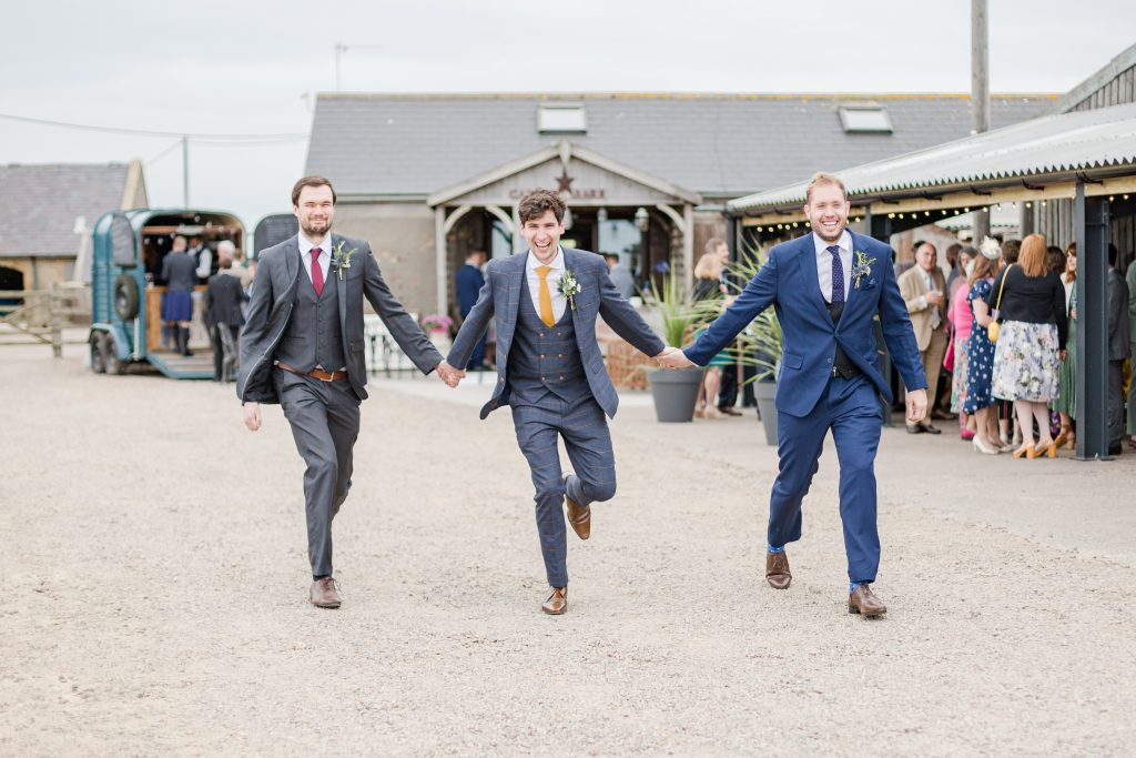 groom and his two bast-men skipping towards the camera with farm behind