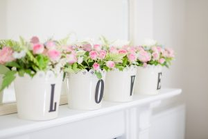 Pink roses in four flower pots spelling LOVE