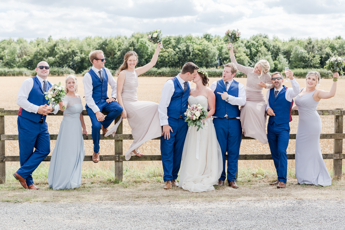 Bridal party sat on fence cheering the bride and groom kiss
