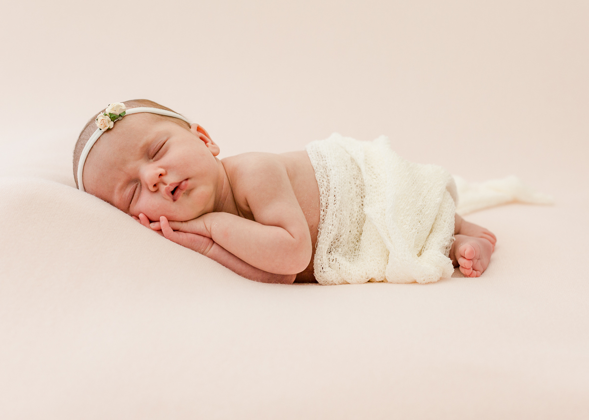 newborn asleep on side with hairband and cream blanket