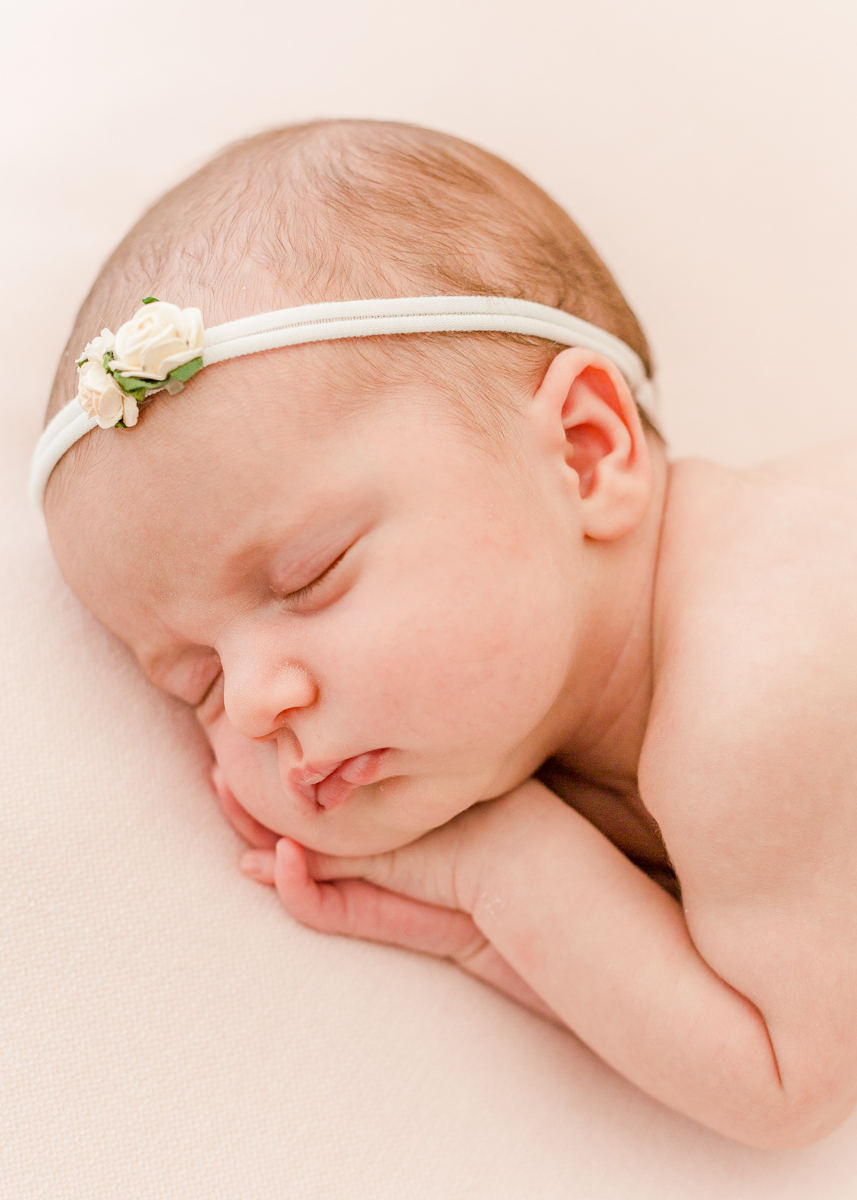 newborn asleep on side with hairband close up