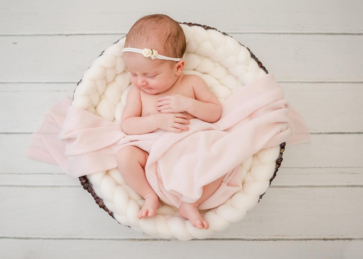 newborn asleep in round basket