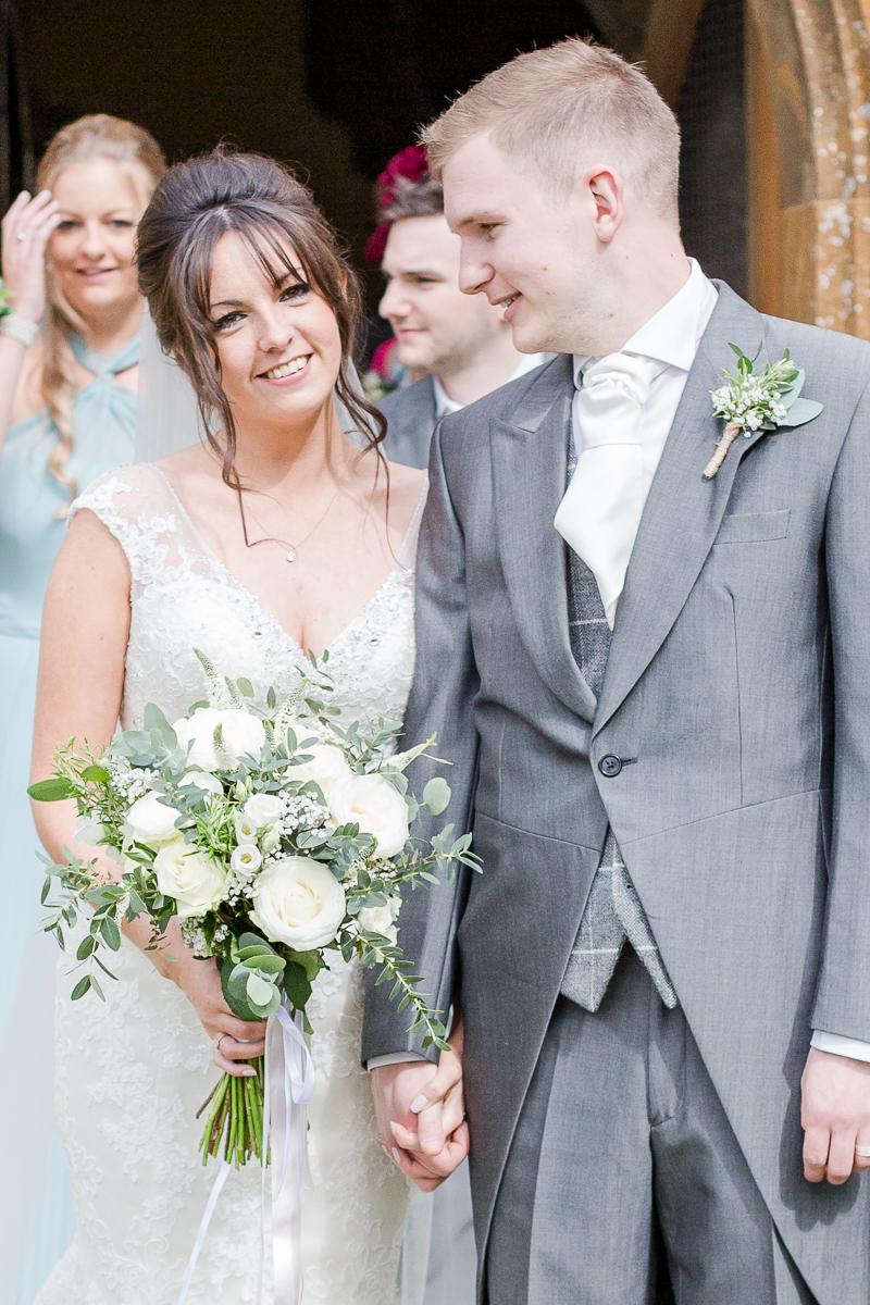 bride and groom in door way of church groom admires bride