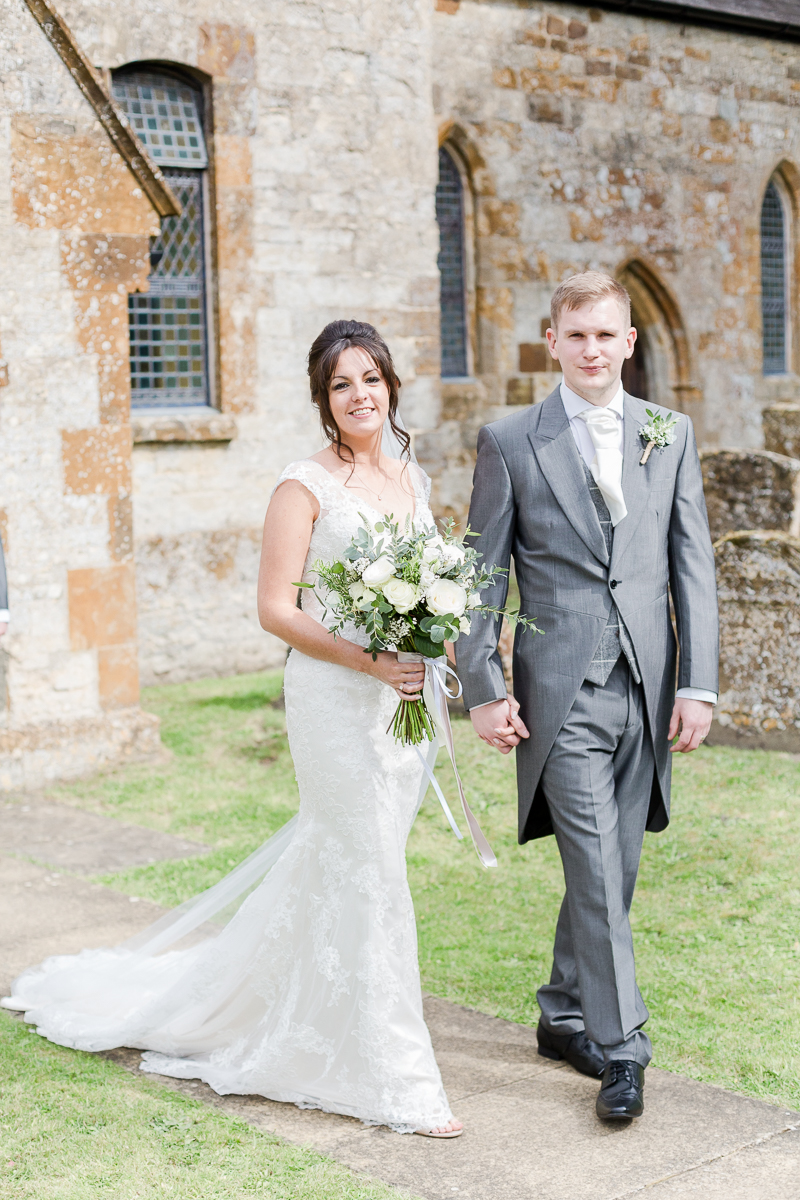 bride and groom walking out of church smiling at camera dress out behind