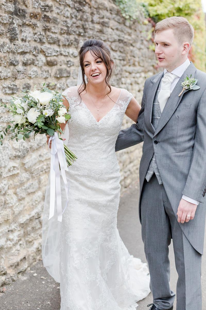 bride and groom walking near stone wall laughing