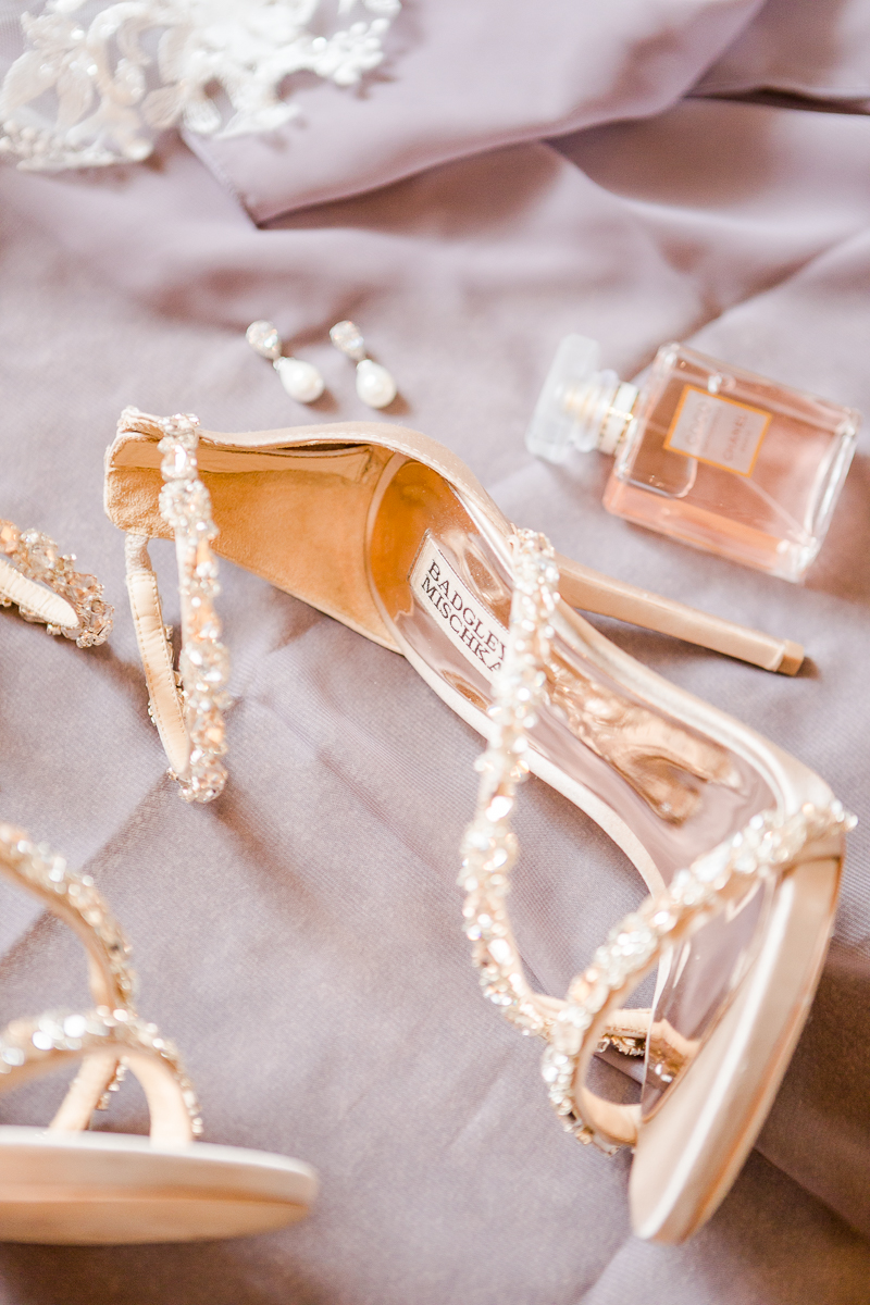 wedding shoes displayed on floor with earrings and perfume