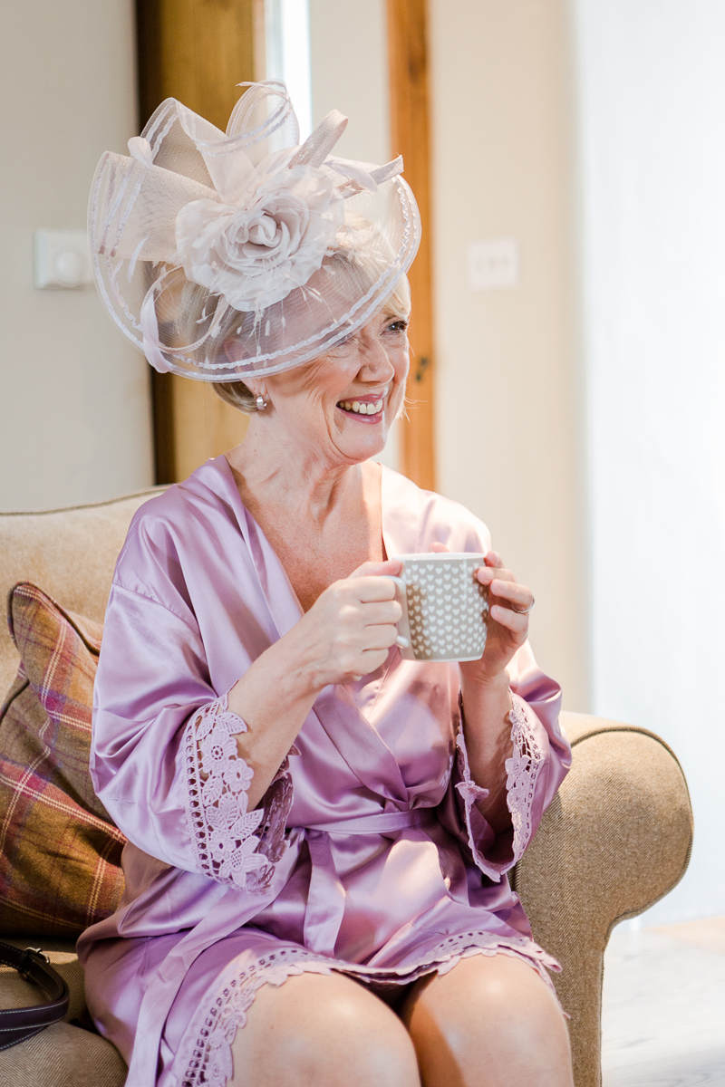 mother of bride wearing hat and purple satin dressing gown drinking tea