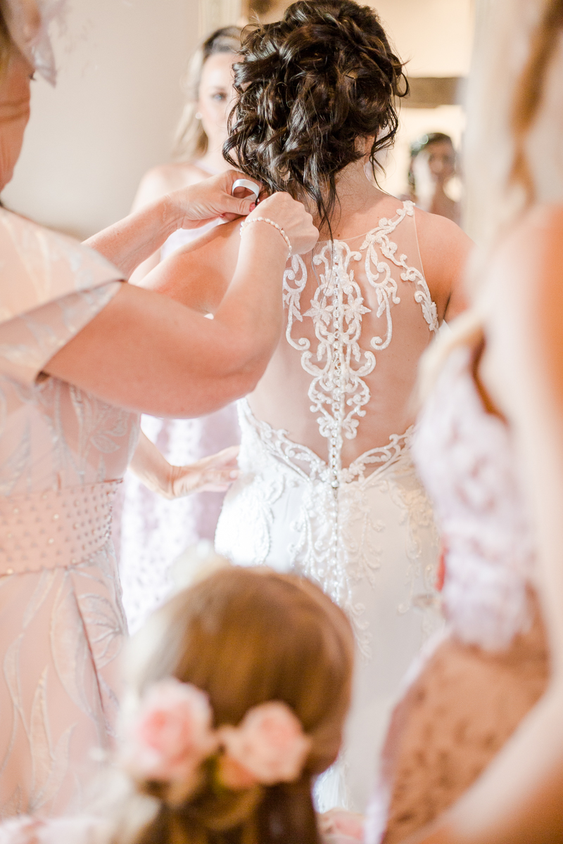 back of brides lace dress with mother of bride touching shoulder