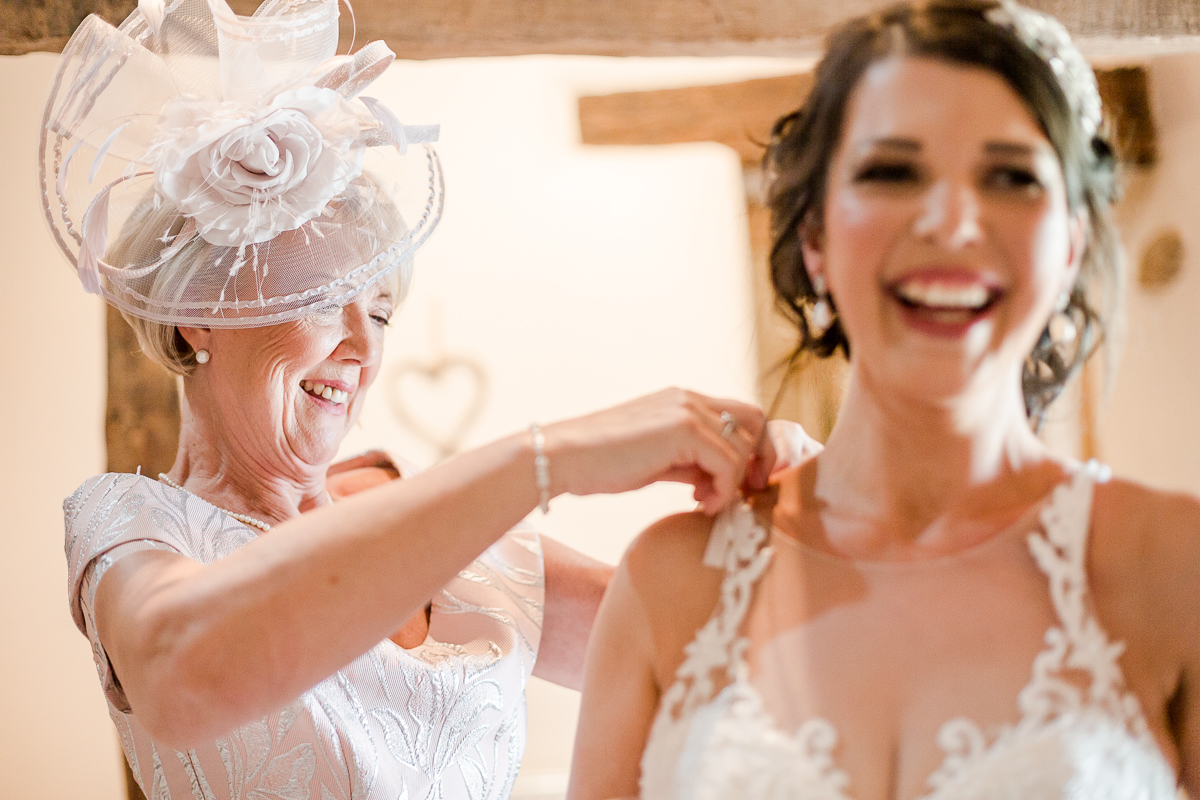 mother of bride fastening wedding dress bride is laughing