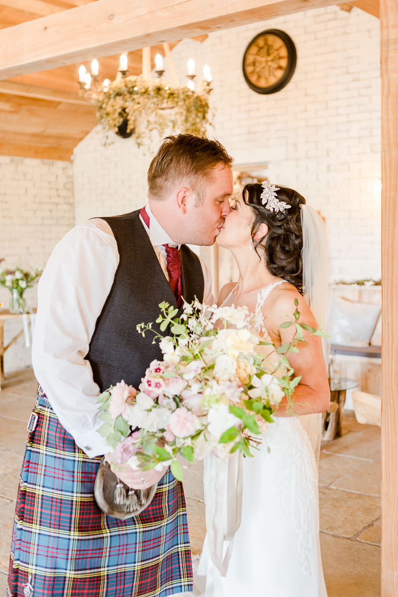 groom wearing quilt kissing bride with bouquet of wild flowers