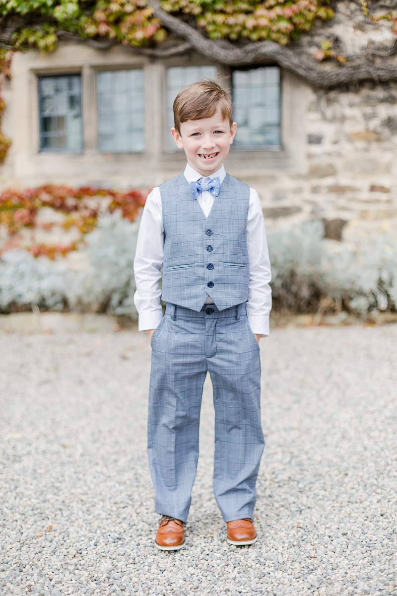 page boy in suit trouser waistcoat with hands in pockets