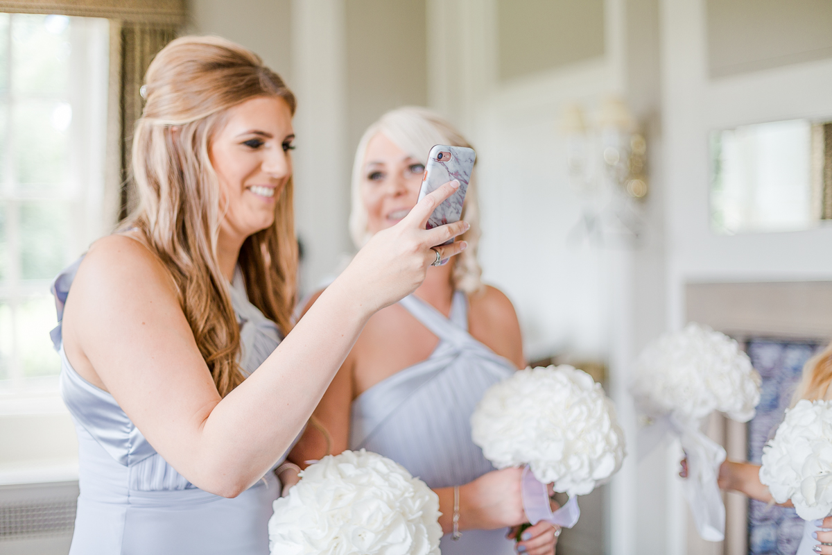 bridesmaids taking photo with phone camera laughing