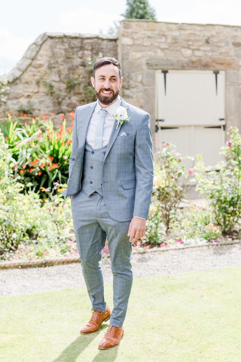 groom wearing grey blue suit in gardens
