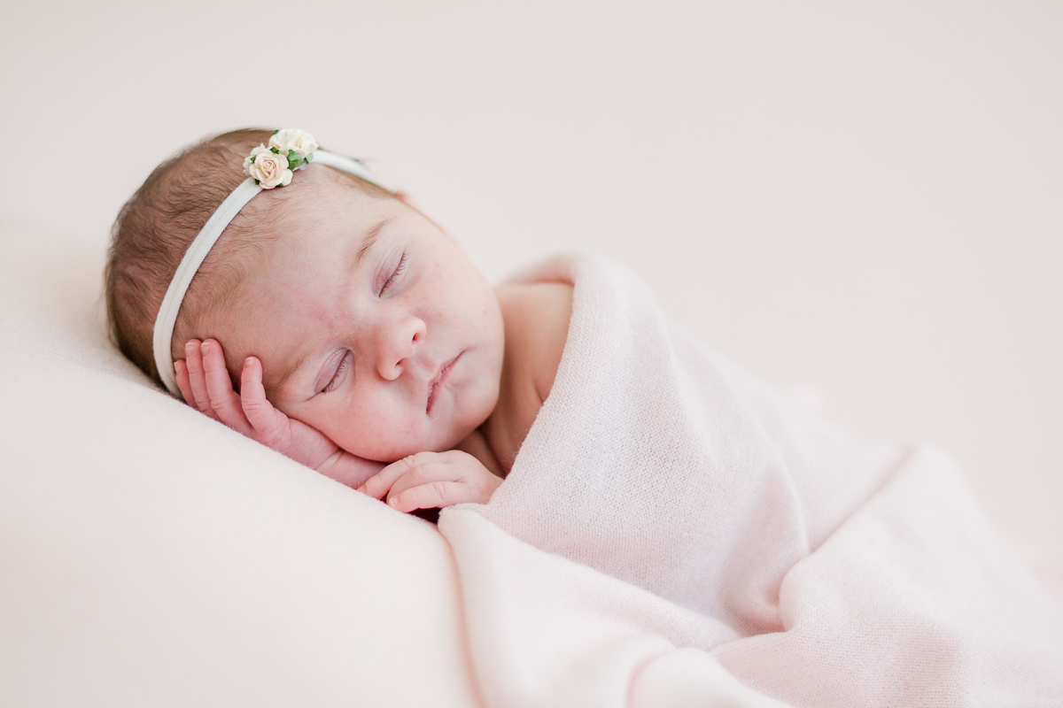 bby girl asleep on hand wrapped in pink