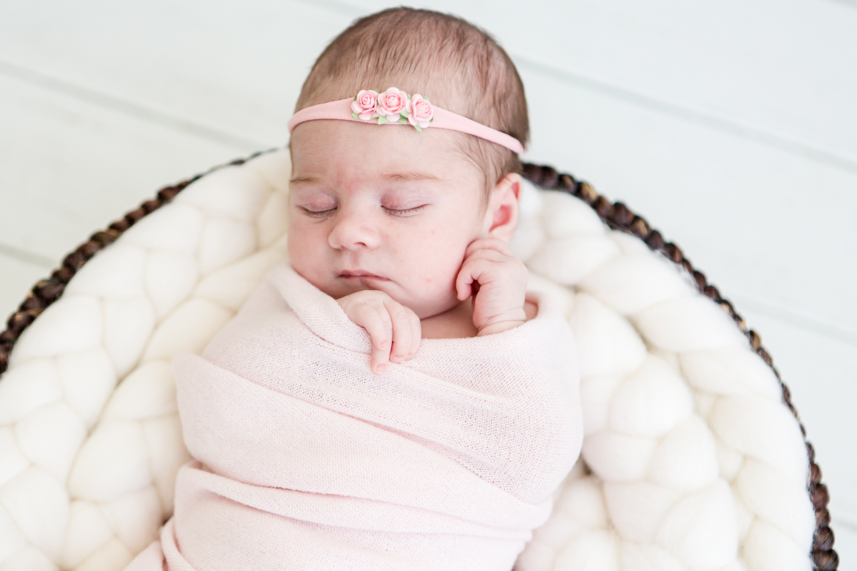 closeup of baby girl wrapped in pink asleep in round basket