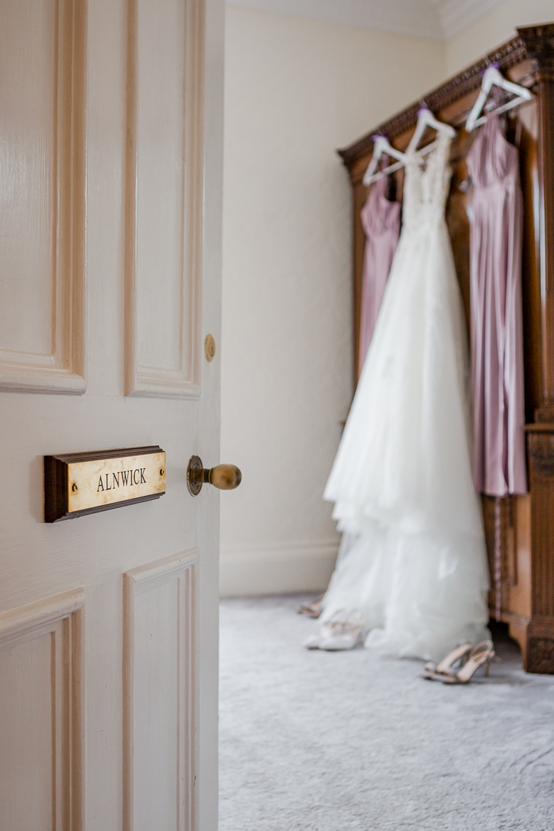 wedding dress and purple bridesmaids dresses hanging on wardrobe