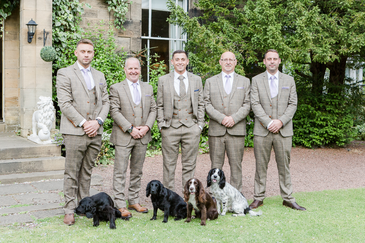 grooms men dressed in tweed posting with four dogs
