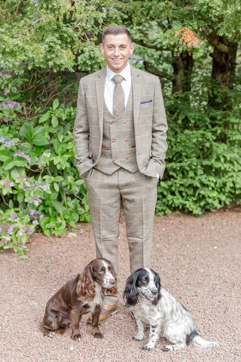 groom in tweed posing with two dogs
