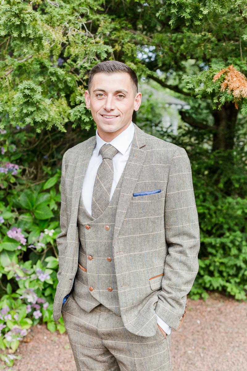 groom in tweed smiling at camera