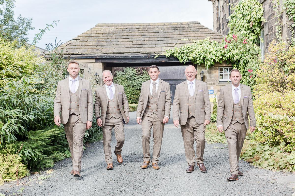 groomsmen walking towards camera on drive way
