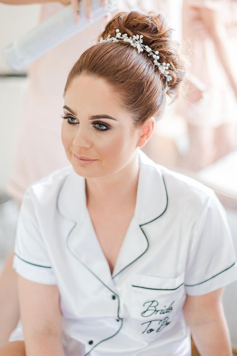 bride getting ready wearing white silk pyjamas
