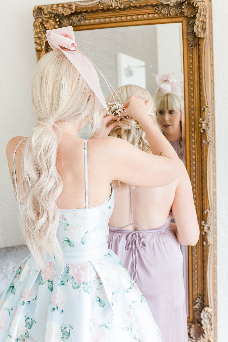 wedding guest in Sumer dress and hat helping with a bridesmaids hair