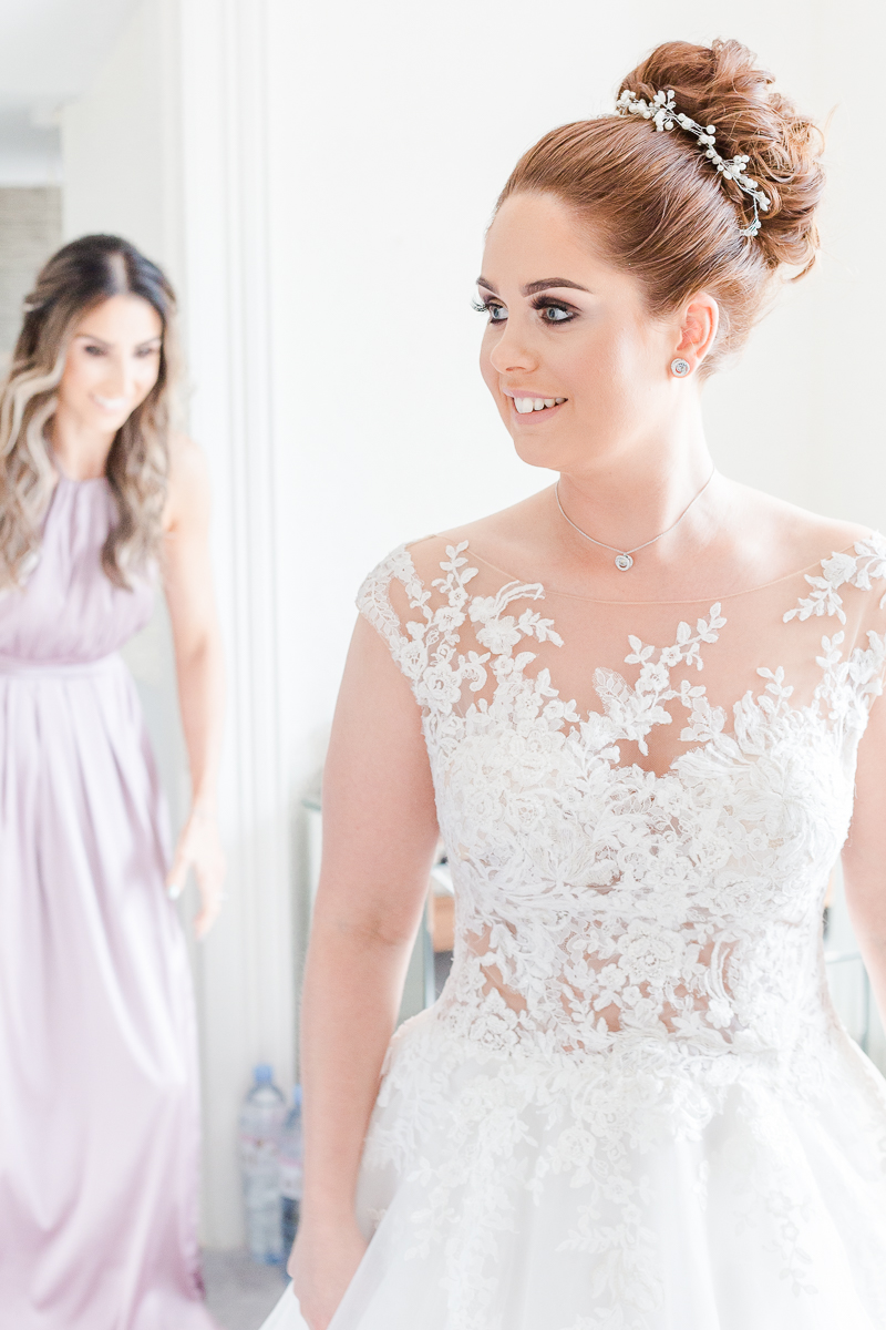 bride in lace wedding dress smiling to the side with bridesmaid in background