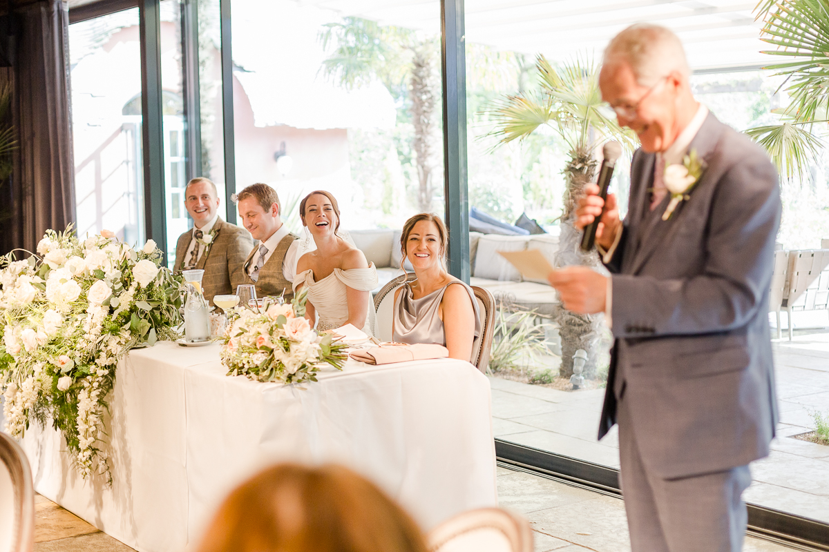father of bride gives speech while bride and groom look on