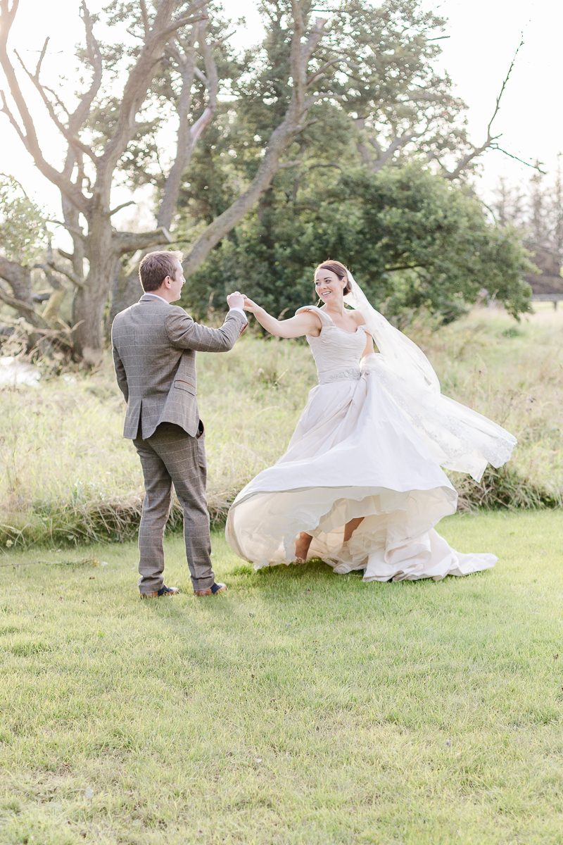 groom swirls bride in green field at sunset