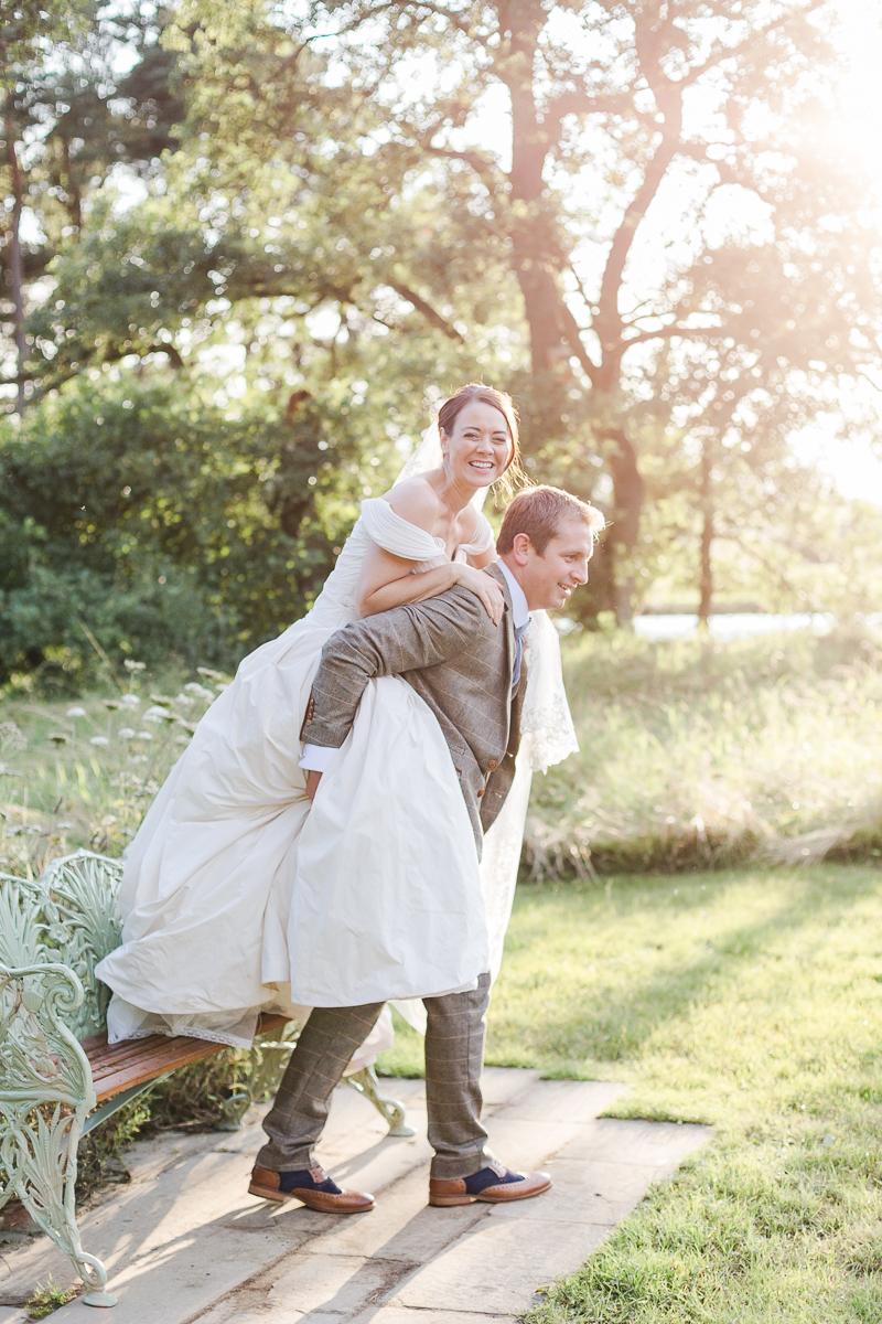 bride has piggy back on groom in field
