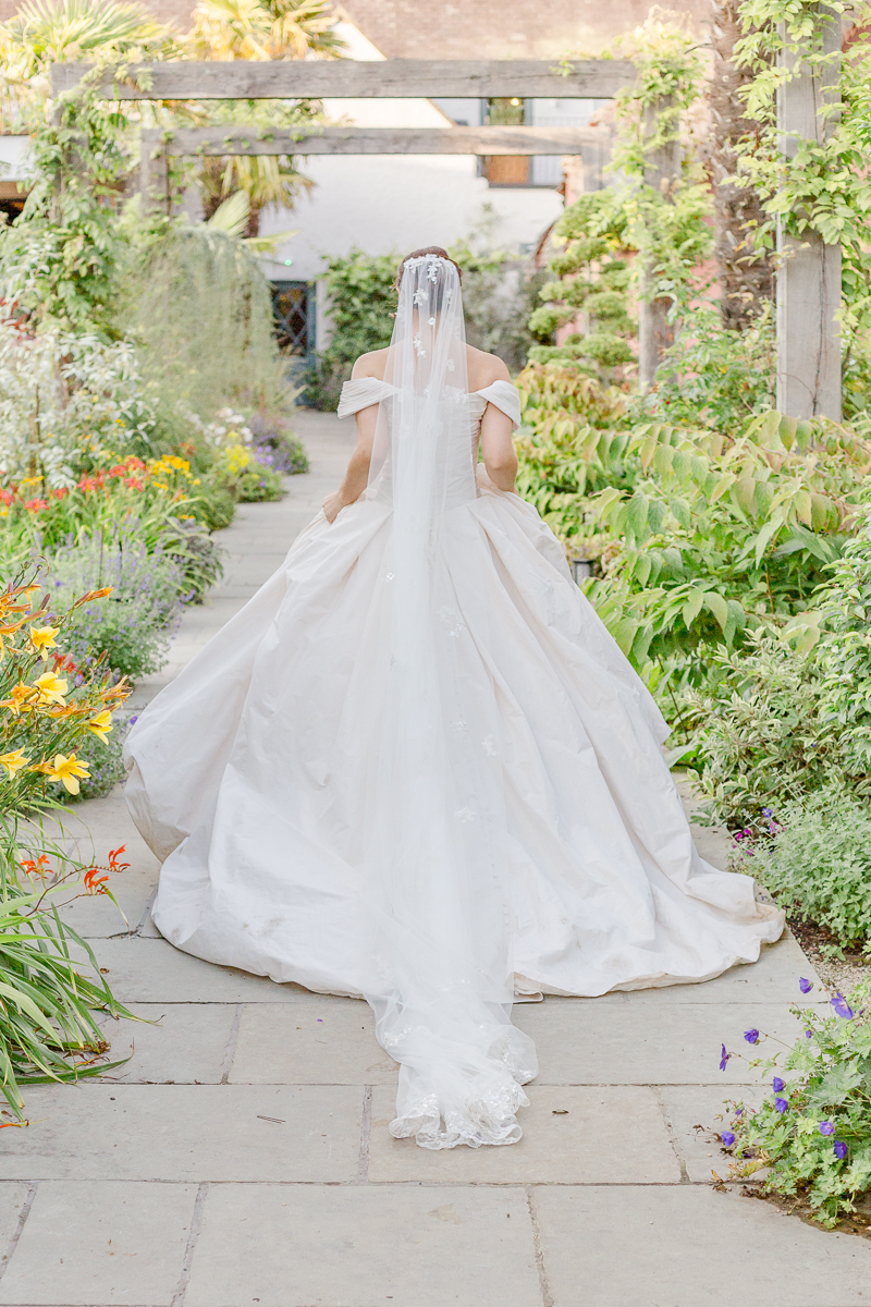 bride and big wedding dress walk through flower garden