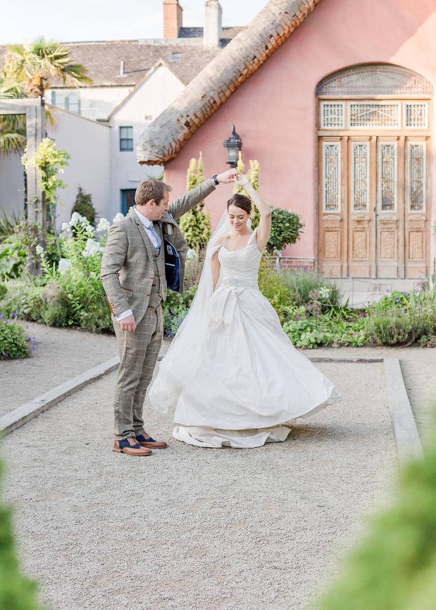 groom swirls bride in gardens