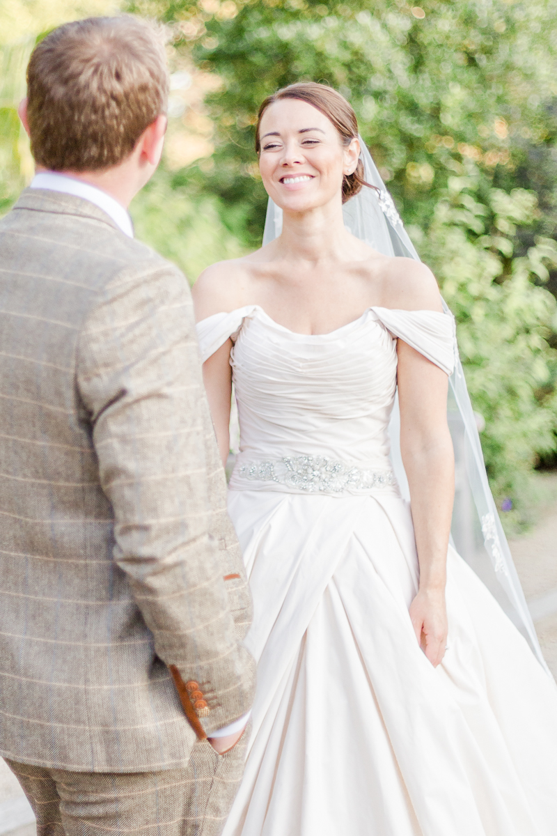 grooms back bride smiling towards camera looking at groom