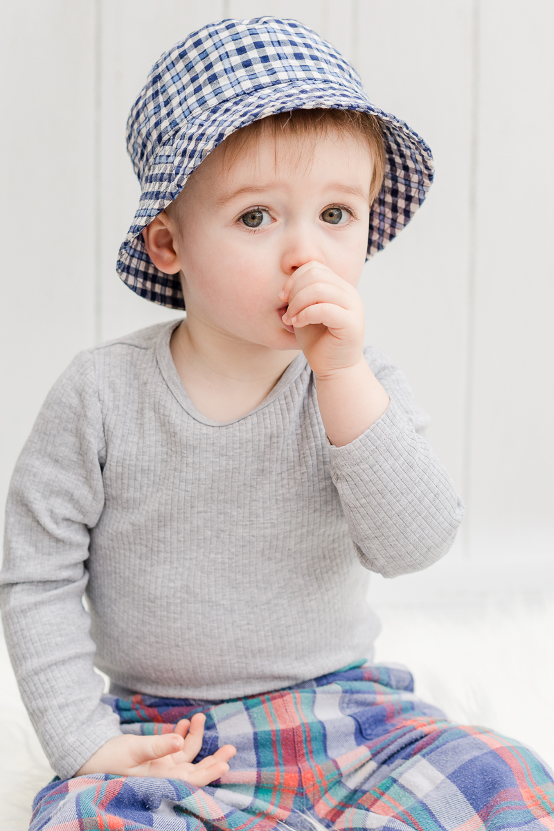2 year old boy sucking thumb with checked hat on in studio