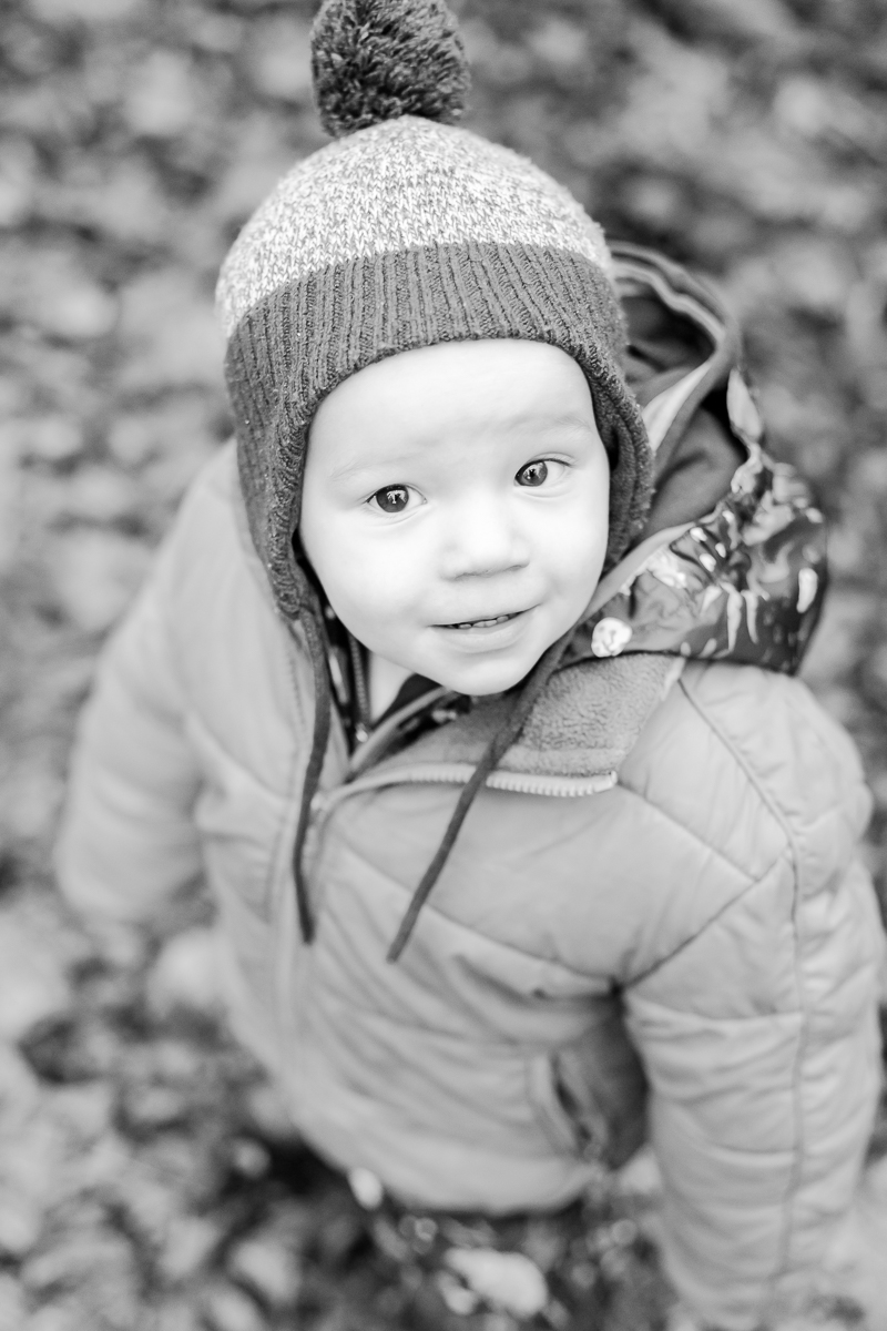 toddler wrapped up in warm clothes smiling up at camera black and white