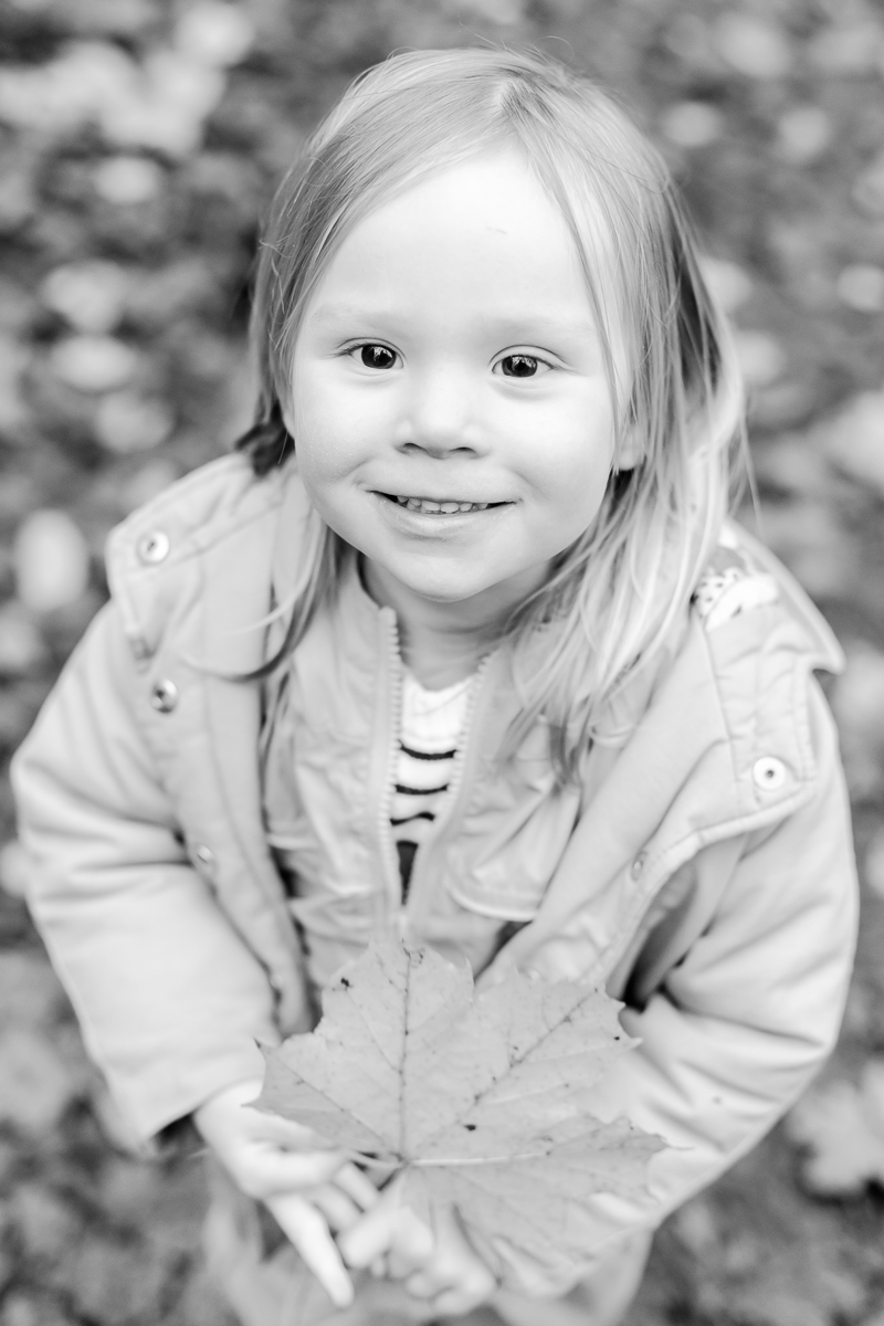 little girl wrapped in warm clothes smiling up at camera